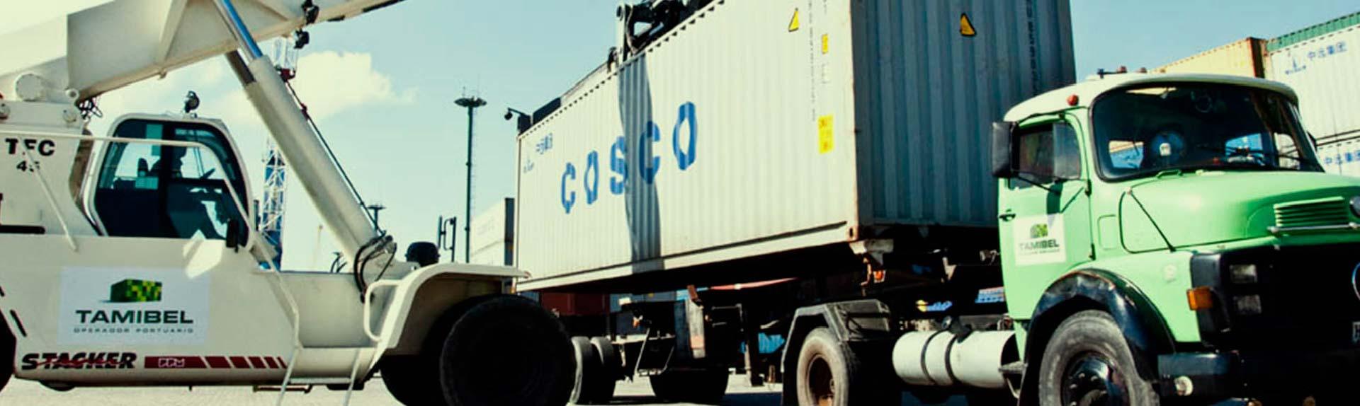 grúa cargando container en camión